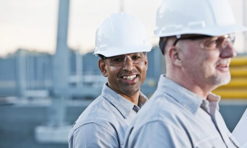 Multiracial men working at industrial site (40s and 50s).  Focus on African American worker.